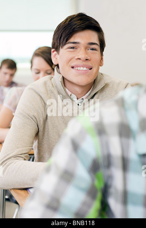 Male high school student working in classroom - Stock Photo