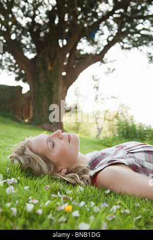 Young woman lying on grass with eyes closed - Stock Photo
