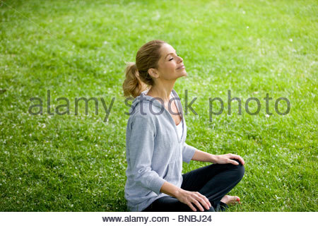 A mid adult woman sitting on the grass - Stock Photo