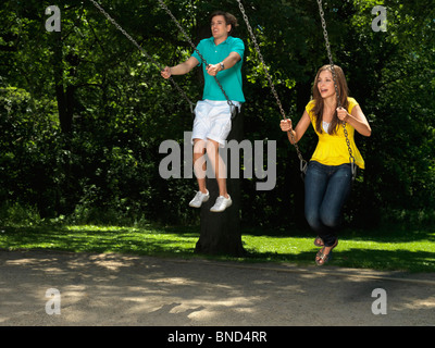 Young couple in their thirties having fun on a swing at children's playground - Stock Photo