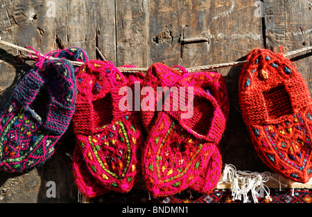 Display of woollen baby shoes outside a shop, Lahic village, Azerbaijan - Stock Photo