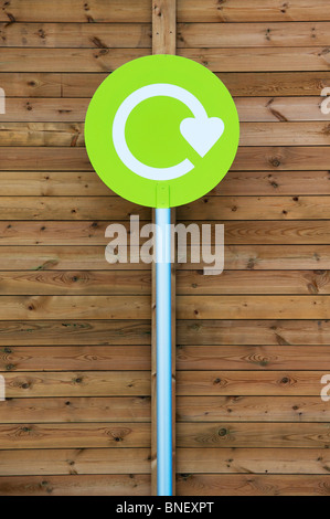 Recycle sign against wooden paneling at a supermarket in England - Stock Photo