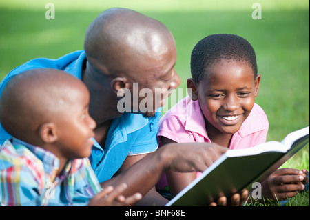 Father reading with children (4-8) on lawn in garden, Johannesburg, Gauteng Province, South Africa - Stock Photo