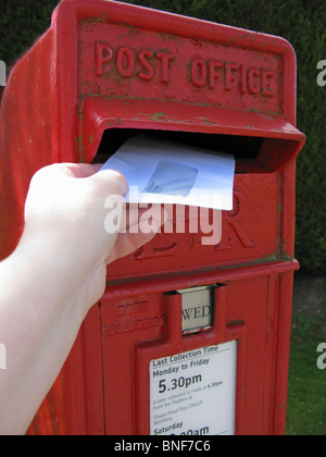 woman posting a letter in a red postbox - Stock Photo