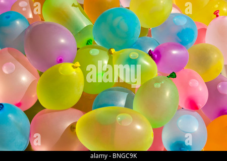 Horizontal close up of hundreds of colourful latex balloons filled with water in preparation for a water fight. - Stock Photo