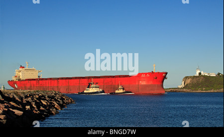 Cargo ship entering the Hunter River on its way to the Port of Newcastle, NSW, Australia. There are three tugs assisting - Stock Photo