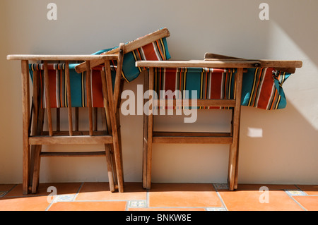 Two old wooden stripey canvas chairs leaning against a white wall on a tiled floor with sunlight on them. - Stock Photo