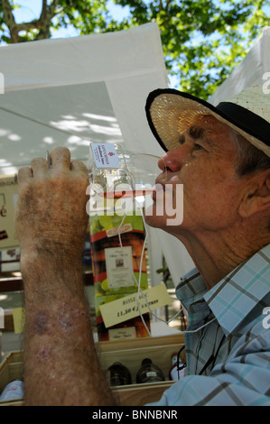 Man wearing a straw hat wine tasting at the AOC Saint Chinian Wine Festival in the Languedoc region of southern - Stock Photo