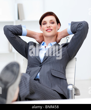 Businesswoman leaning back on a chair with his feet on the desk - Stock Photo