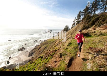 Woman trail running along the Oregon coast. - Stock Photo
