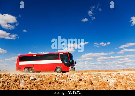 A bus drives along a dirt road in outback Queensland, near Birdsville, Queensland, AUSTRALIA. - Stock Photo