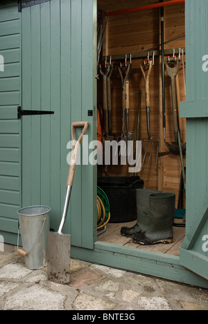 Spade and muddy boots by a garden shed. - Stock Photo