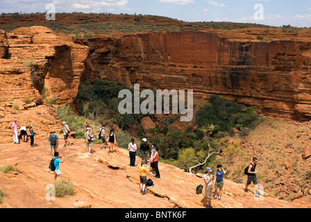 Tourists on the edge of the canyon. Watarrka (Kings Canyon) National Park, Northern Territory, AUSTRALIA. - Stock Photo