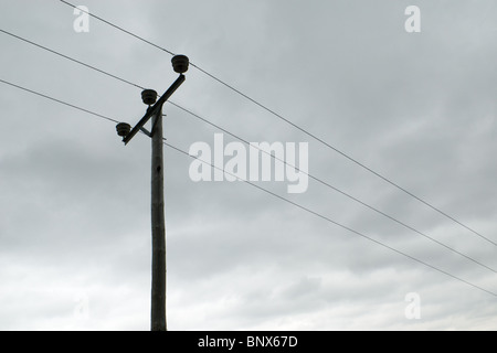 Three phase electrical power cables against a backdrop of grey sky, Ardnamurchan, Scotland - Stock Photo