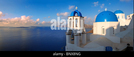 Oia, ( Ia ) Santorini - Blue domed Byzantine Orthodax churches, - Greek Cyclades islands - Panoramic - Stock Photo