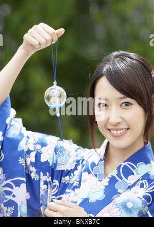 Young woman holding wind chime - Stock Photo
