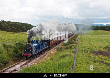 Restored Caledonian Railway 0-6-0 steam engine 828 steams along on Strathspey Railway track between Broomhil and - Stock Photo