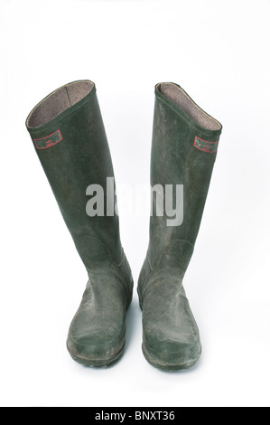 A pair of old used worn green wellington boots against a white background - Stock Photo