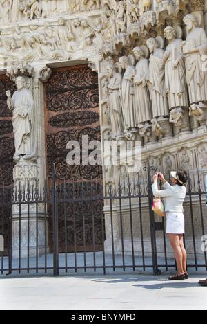 Japanese tourist taking photograph at Notre Dame Paris France - Stock Photo