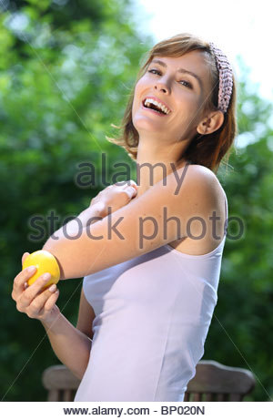 woman rubs the elbow with a lemon - Stock Photo