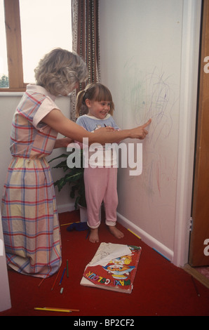 mother telling her daughter off for scribbling on the wall - Stock Photo