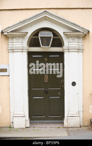 Green painted front door no. 9 with brass letterbox knocker knob triangular pediment and architrave of Georgian - Stock Photo