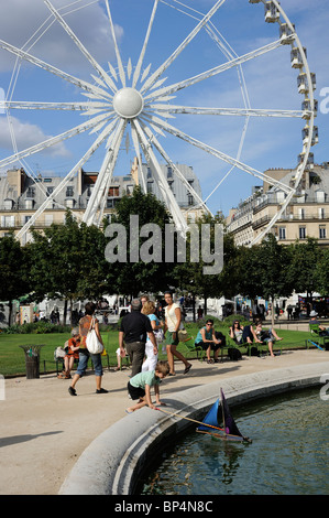 A kid playing with toy yacht at a pond, tuileries garden, Paris, France - Stock Photo