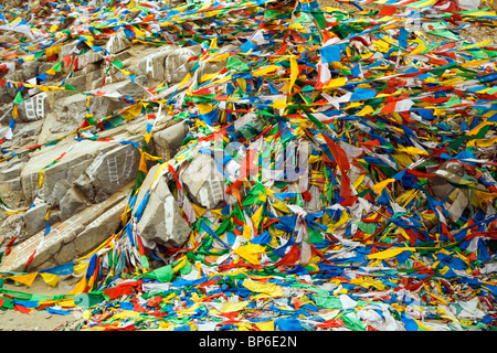Prayers flags blow against white painted ladders at a Tibetan Burial site - Stock Photo