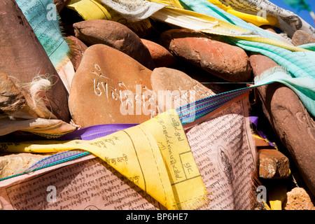 Tibetan prayer flags across sanskrit engraved stones at Lake Namsto, Tibet. - Stock Photo