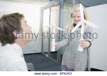 A businessman and young girl blowing the sails of a model wind turbine - Stock Photo