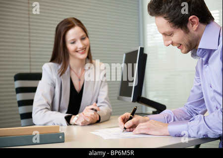 Man signing documents with a female real estate agent sitting in front of him - Stock Photo