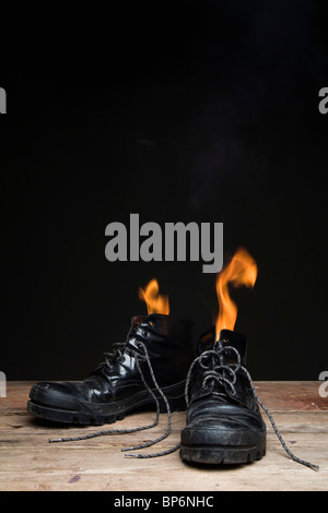 Leather boots on fire - Stock Photo