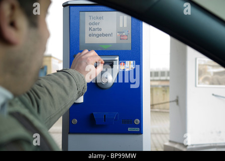 Man inserting ticket in parking machine Berlin Germany - Stock Photo