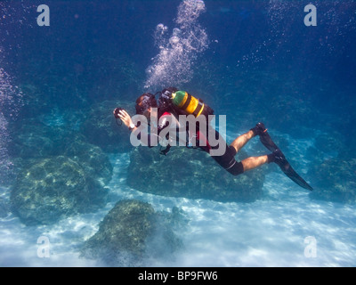 A scuba diver instructor is taking underwater photos of his pupils. The Blue Lagoon, near Cape Greco, Cyprus, Europe. - Stock Photo