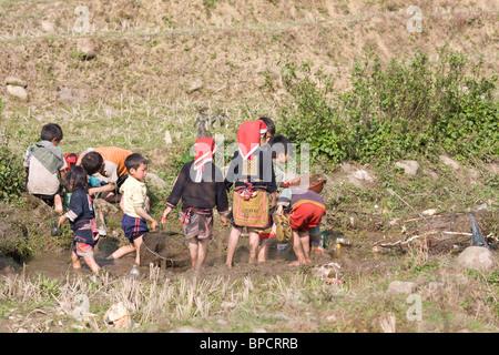 Red Dzao children playing in the mud - Stock Photo