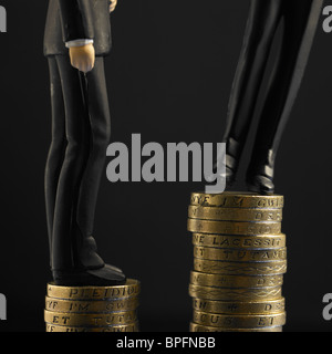 Two Figures In Black Suits Standing On Top Of Unequal Piles Of Pound Sterling Coins, One Toppling - Stock Photo