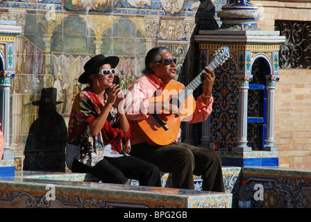 Buskers sitting on a tiled bench in the Plaza de Espana, Seville, Seville Province, Andalucia, Spain, Western Europe. - Stock Photo