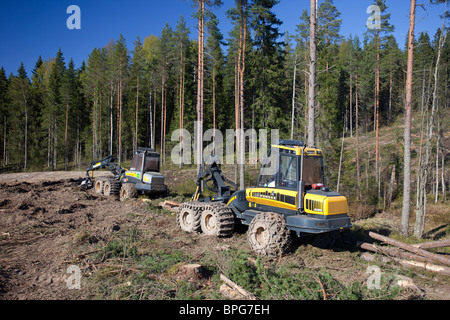 Ponsse Buffalo forwarder and Ponsse Beaver forest harvester at clear-cutting area , Finland - Stock Photo