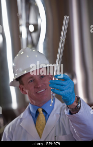 Scientist checking a sampling tube in a brewery - Stock Photo