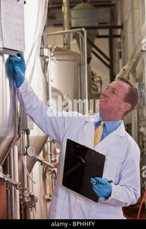 Scientist checking records of fermentation tanks in a brewery - Stock Photo