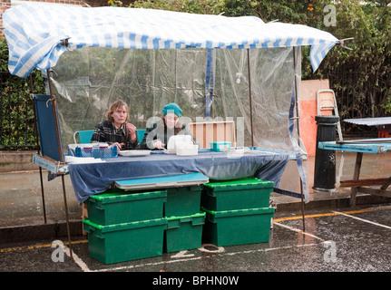 Two stallholders eating in their stall on a rainy dayPortobello Market London UK - Stock Photo