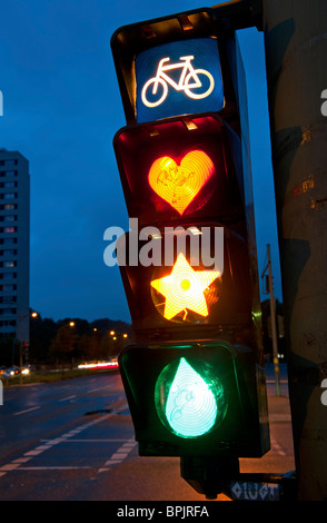 Detail of cyclist traffic lights with lamps painted to show heart, star and tear in Berlin Germany - Stock Photo
