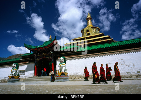 Local monks passing Gong Tang pagoda at Labrang Lamma Buddhist monastery (Yellow Hat) in the town of Xiahe in Gansu. - Stock Photo