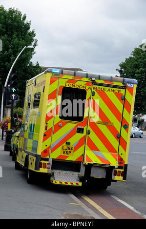 London Ambulance parked half on pavement with lights flashing whilst attending an emergency - Stock Photo