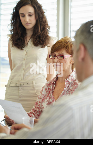 Older business woman reading document - Stock Photo