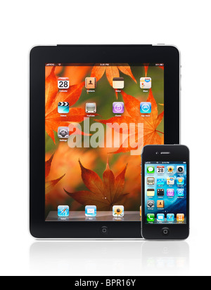 Apple iPad 3G tablet computer and iPhone 4 smartphone with desktop icons on their displays isolated on white background. - Stock Photo