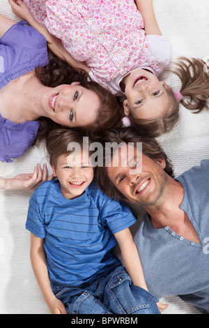 Happy family lying on rug - Stock Photo