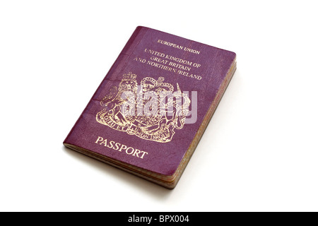 A well travelled British passport on a white background - Stock Photo