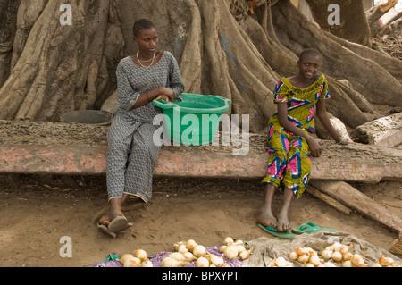 Girls sitting under a kapok tree, selling potato in the market, Elinkine, Casamance, Senegal - Stock Photo