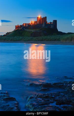 Bamburgh Castle at sunrise on the east coast of Northumberland, England. - Stock Photo